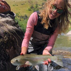 Cross Current Insurance fly fishing ambassador Abbie Schuster holding rainbow trout
