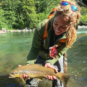 Cross Current Insurance fly fishing ambassador Abbie Schuster holding brown trout