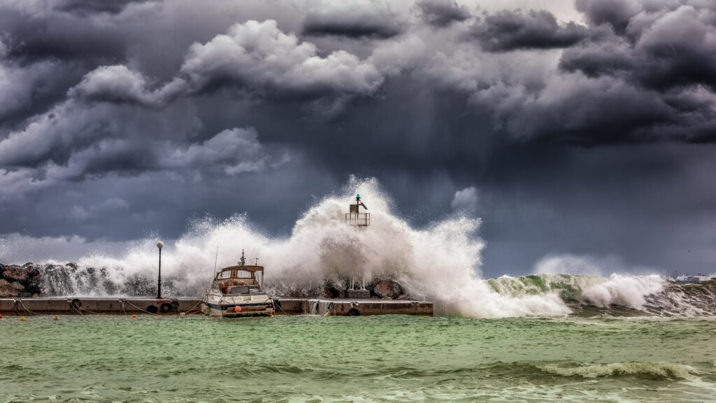 Wave on stormy seas crashing into boat and lighthouse