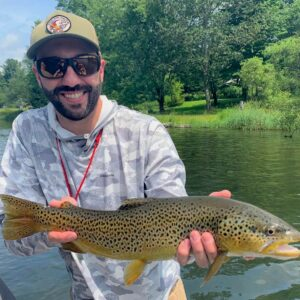 Cross Current Insurance's Dan Phelan showing the brown trout he caught fly fishing.