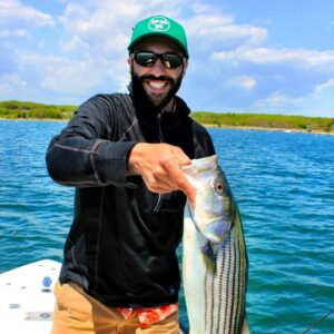 Cross Current Insurance's Sales Manager, Dan Phelan, displaying his striper catch while fly fishing.