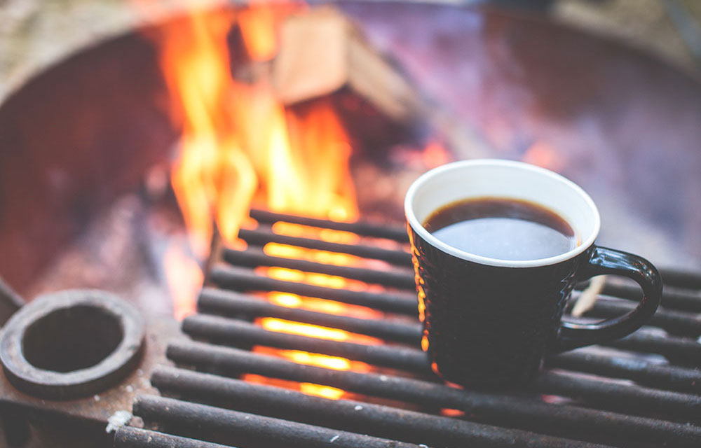 Morning coffee around the campfire at fly fishing lodge